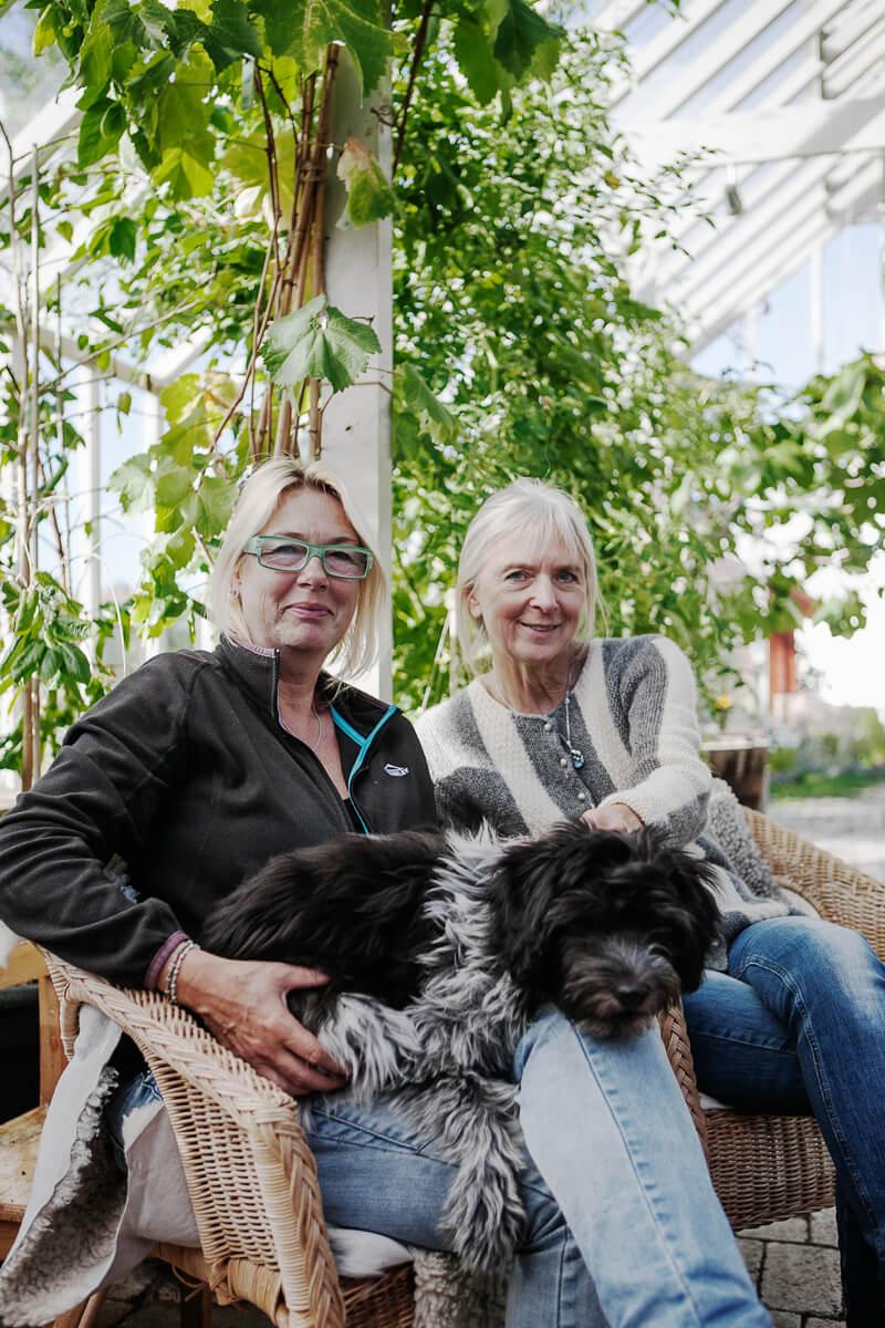 Två kvinnor och en hund sitter i växthuset