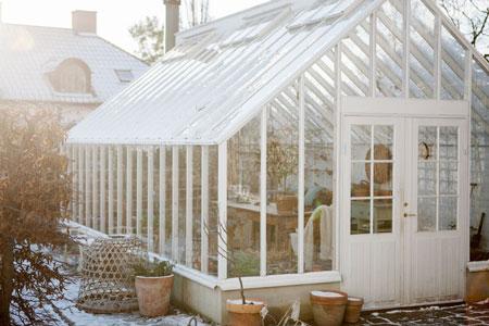 Ett vitt växthus i på vintern.