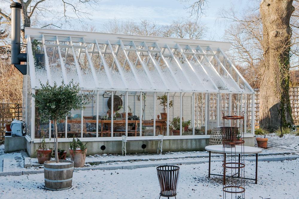 Växthus med sadeltak täckt med ett lätt snötäcke.
