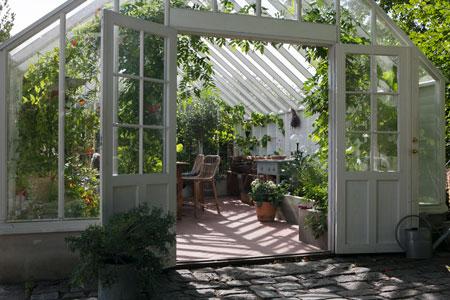 Vitt växthus i trä med sadeltak.