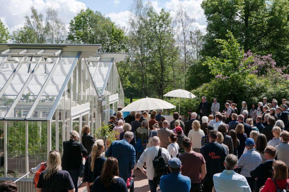 Folksamling framför ett stort växthus