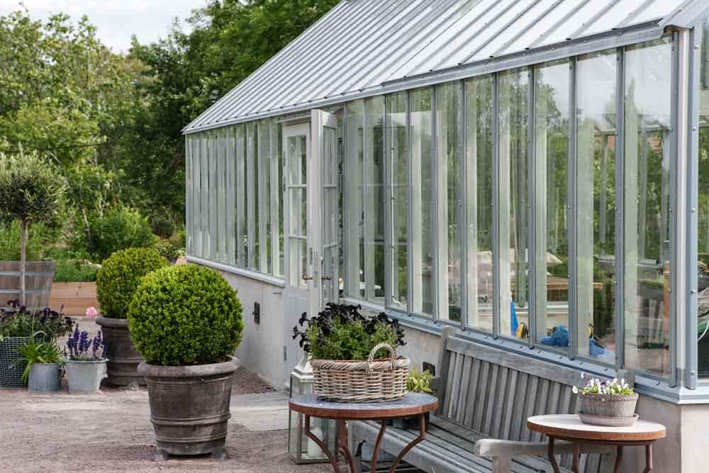 Ett grått växthus med både isoler- och enkelglas.