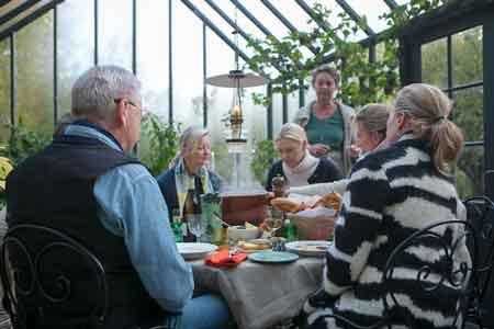 Gäster runt dukat middagsbord i växthus.