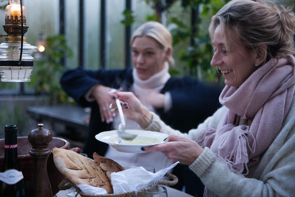 Soppa serveras till sex gäster kring runt bord i växthus.