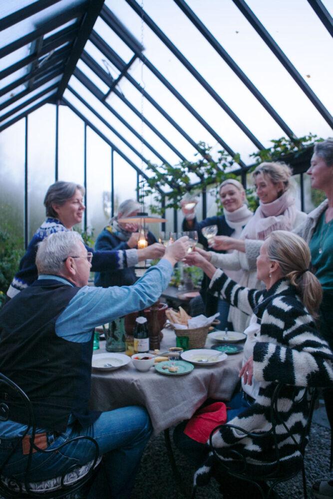 Sex gäster som tackar värdinnan med en skål i växthuset.