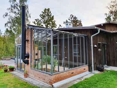 Ett växthus med sadeltak sammanbyggt med ett modert trähus.