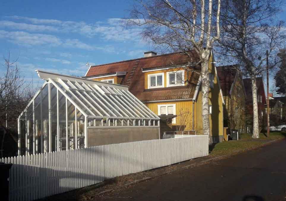 Ett nybyggt växthus med sadeltak och mur på en långsida.