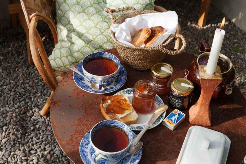 Uppdukat bord med tekoppar, toast och marmelad i växthus.