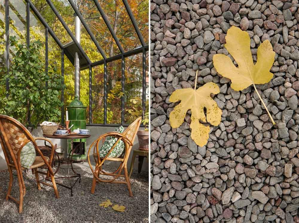Bord uppdukat med tekoppar framför kakelugn i växthus.