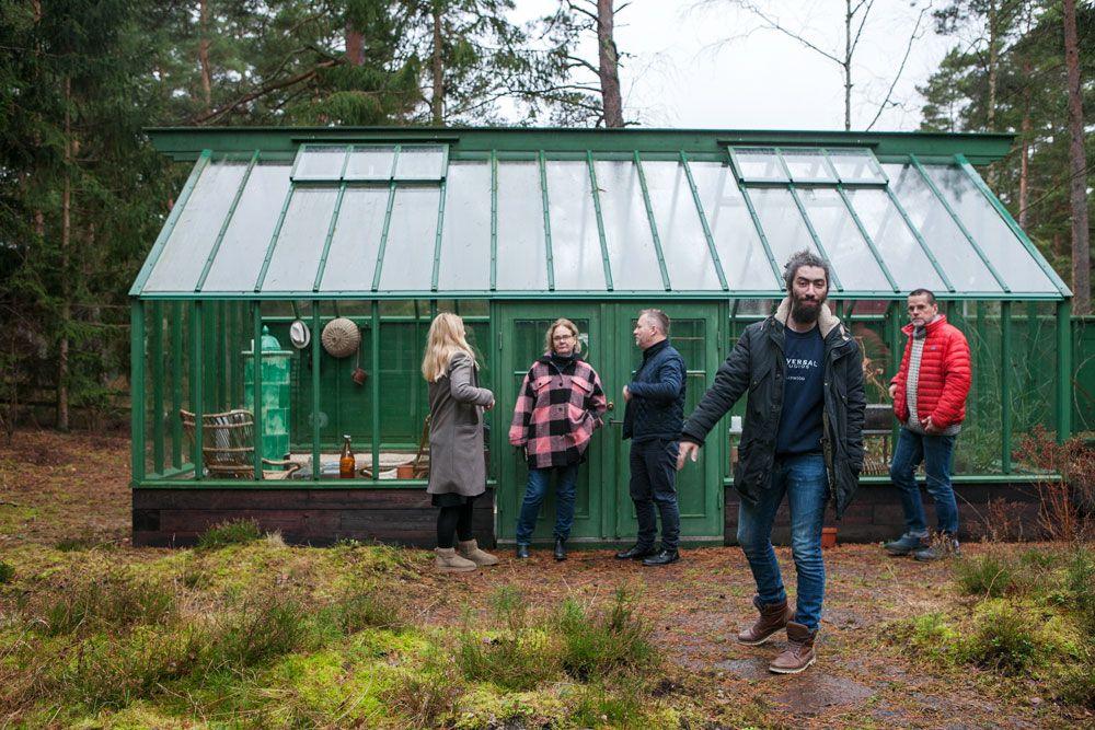 Två män och två kvinnor framför ett grönt växthus.
