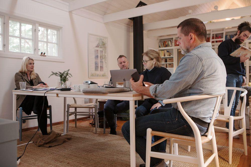 Två kvinnor och två män sitter runt ett bord och en man står bredvid.