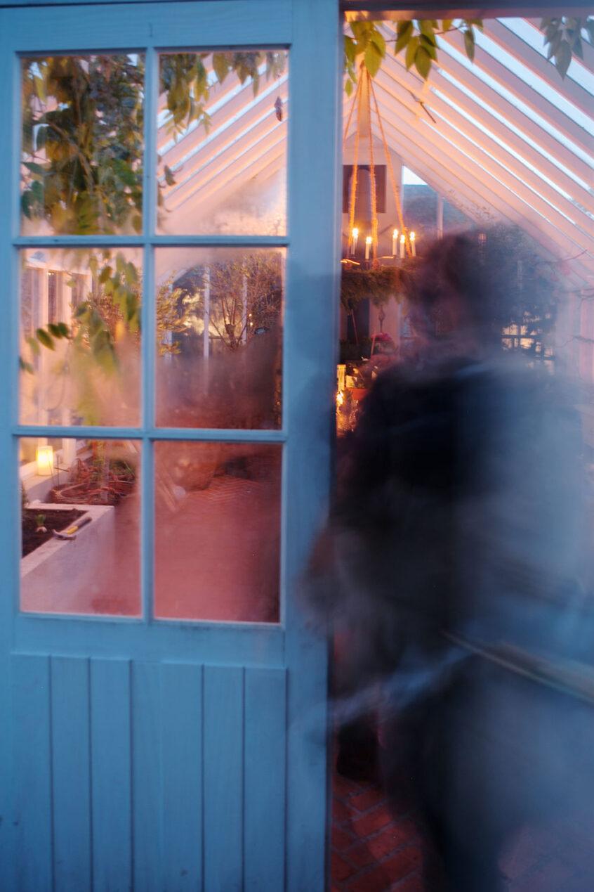 En oskarp människa stiger in genom dörren till ett växthus.