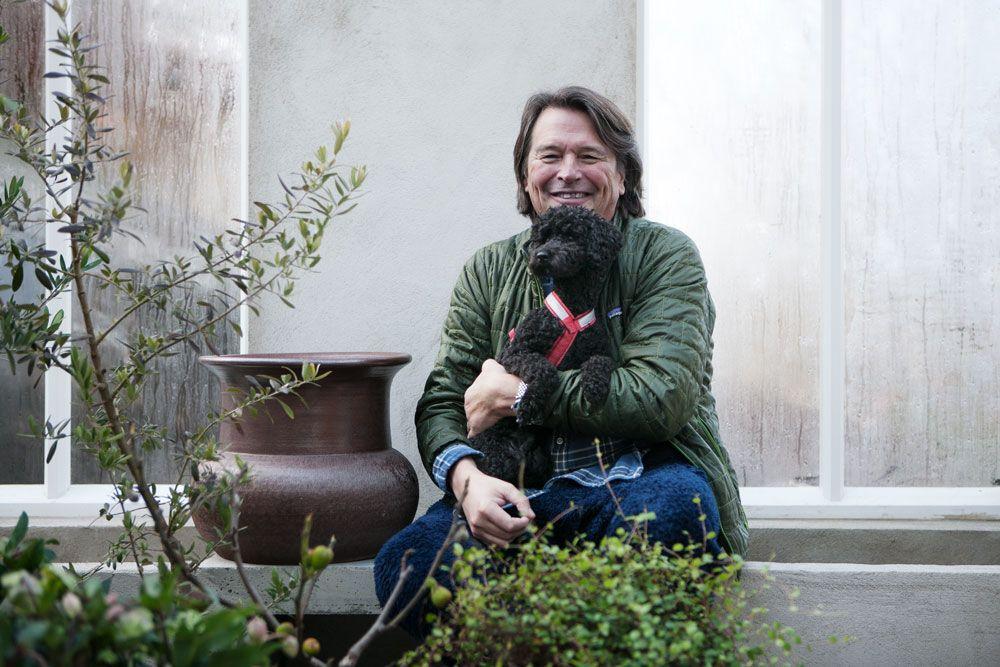 man med liten hund sittandes i ett växthus.