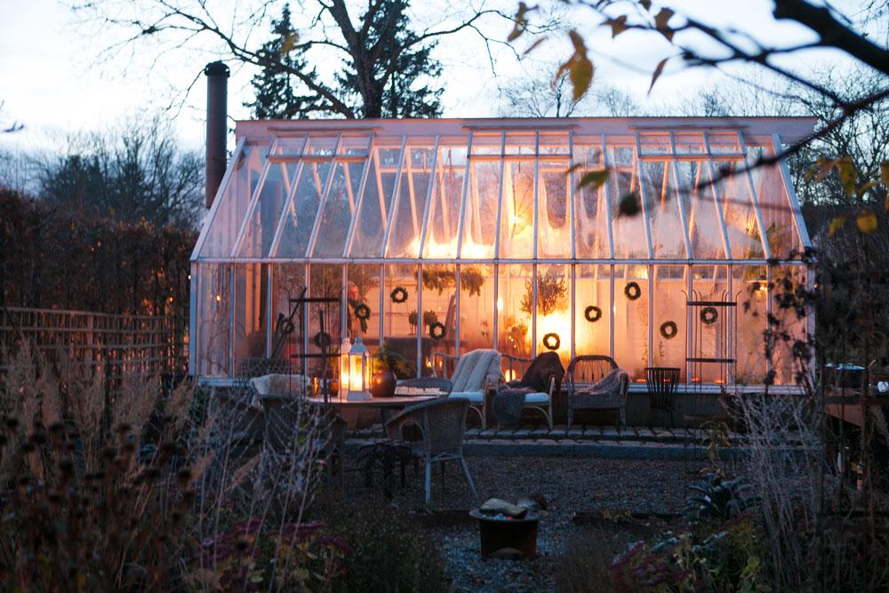 Upplyst växthus i vintermörker.