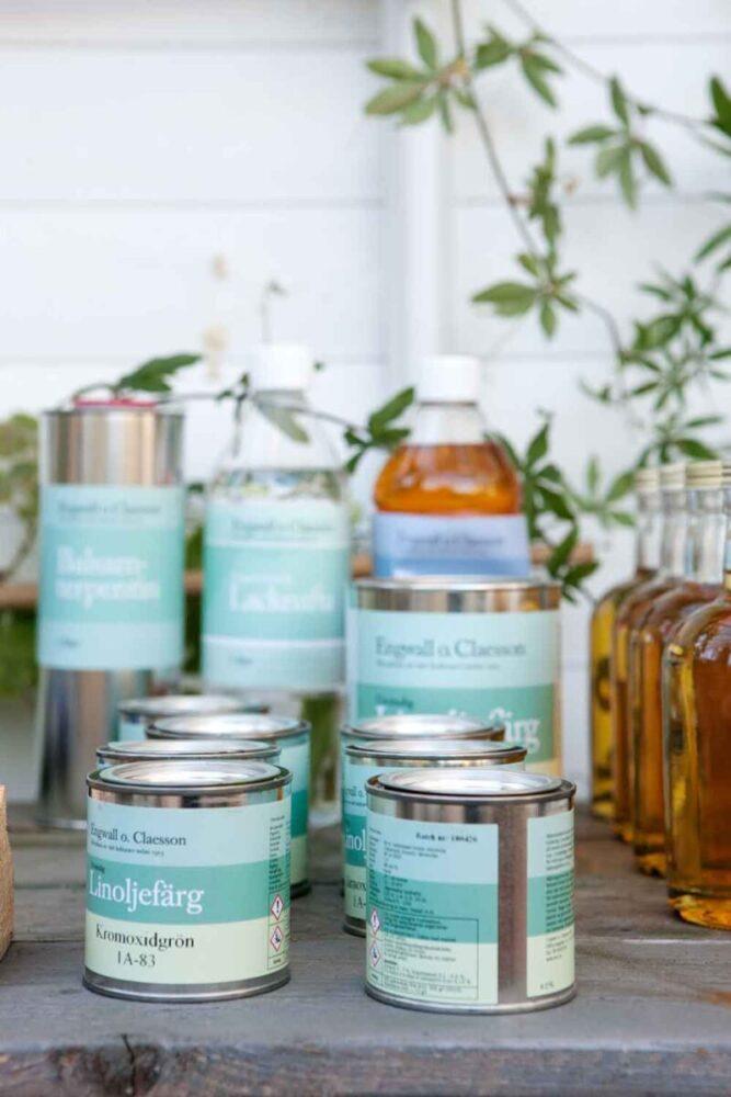 Linolja i flaskor och färgburkar på bord i växthus.