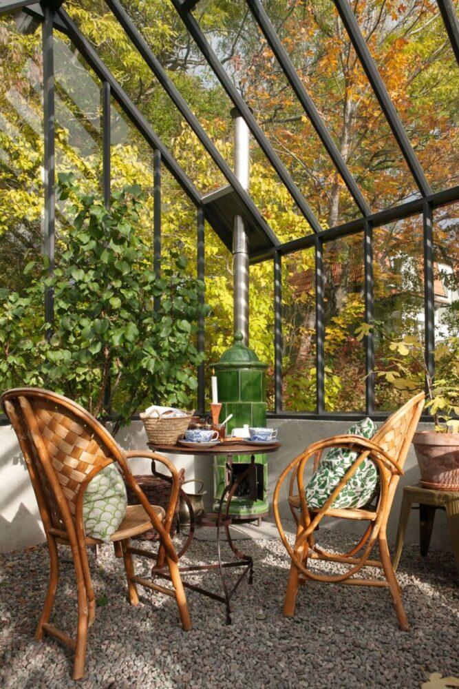 Ett uppdukat runt bord och två rottingstolar framför en braskamin i ett grått växthus.