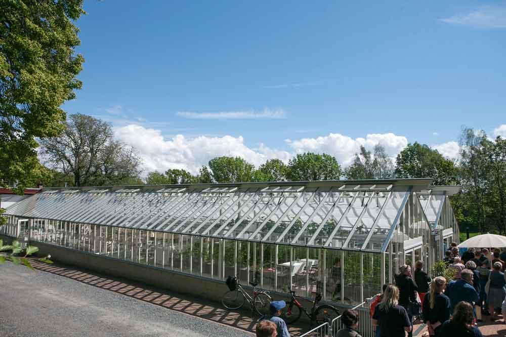 Folksamling framför stort växthus
