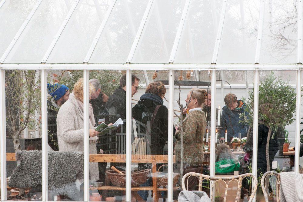 En grupp människor bakom växthusglas.