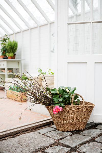 Korg med kvistar i växthusdörr.