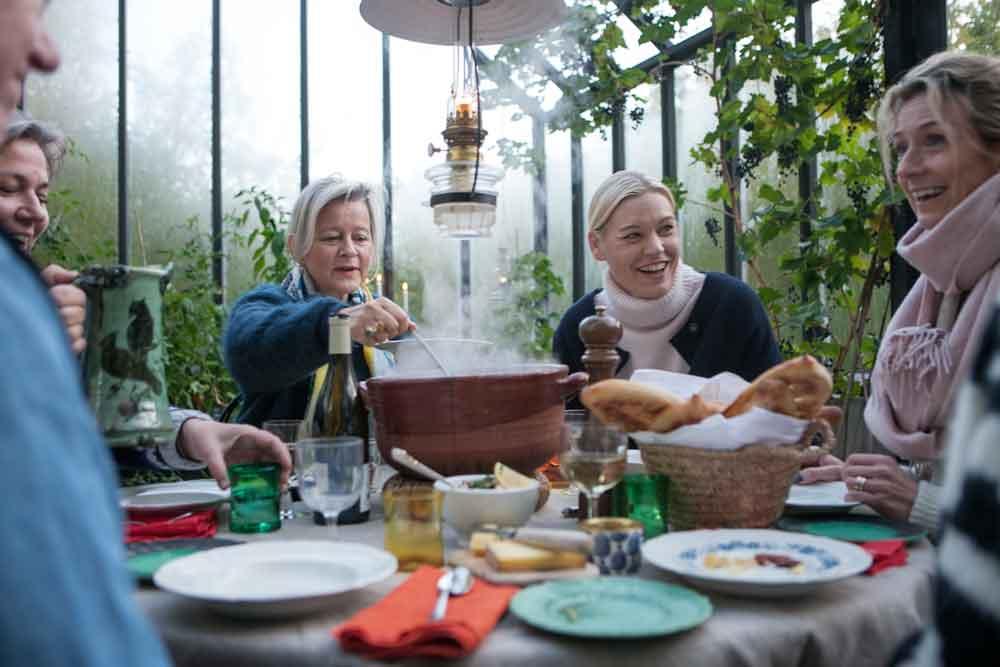 Människor runt dukat bord i växthus.