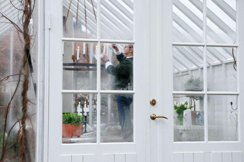 Kvinna tänder ljuskrona i växthus.