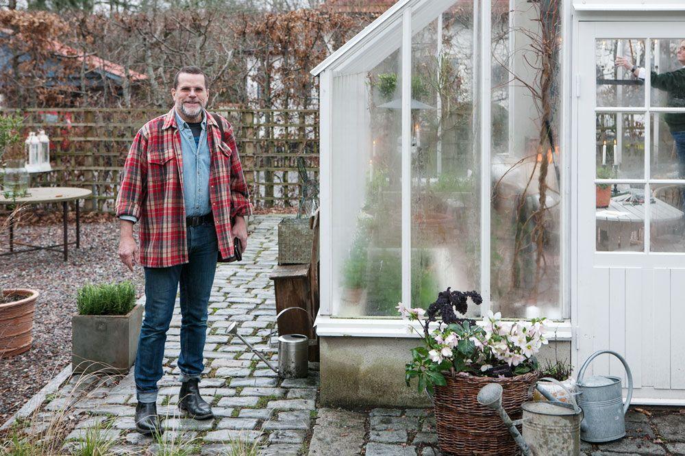 Man utanför växthus i trä och glas.