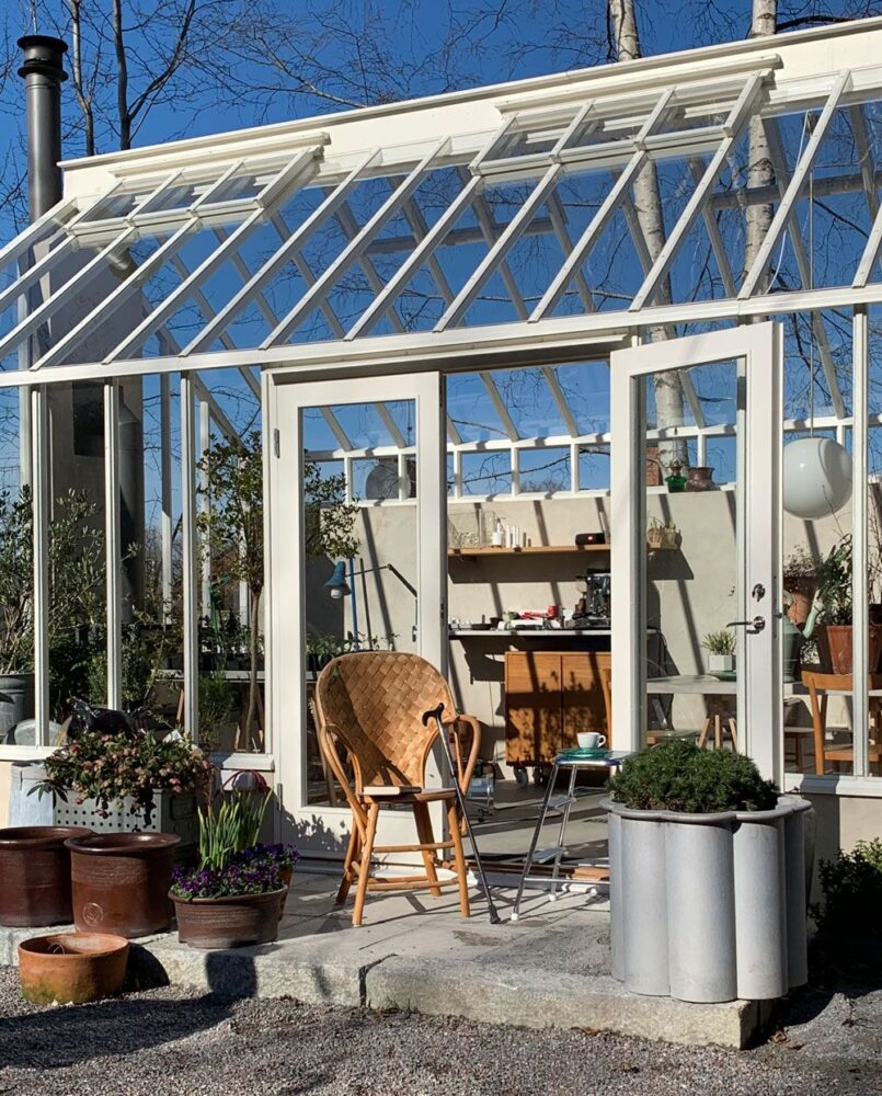 korstol och krukodlade växter på trappa framför växthus.