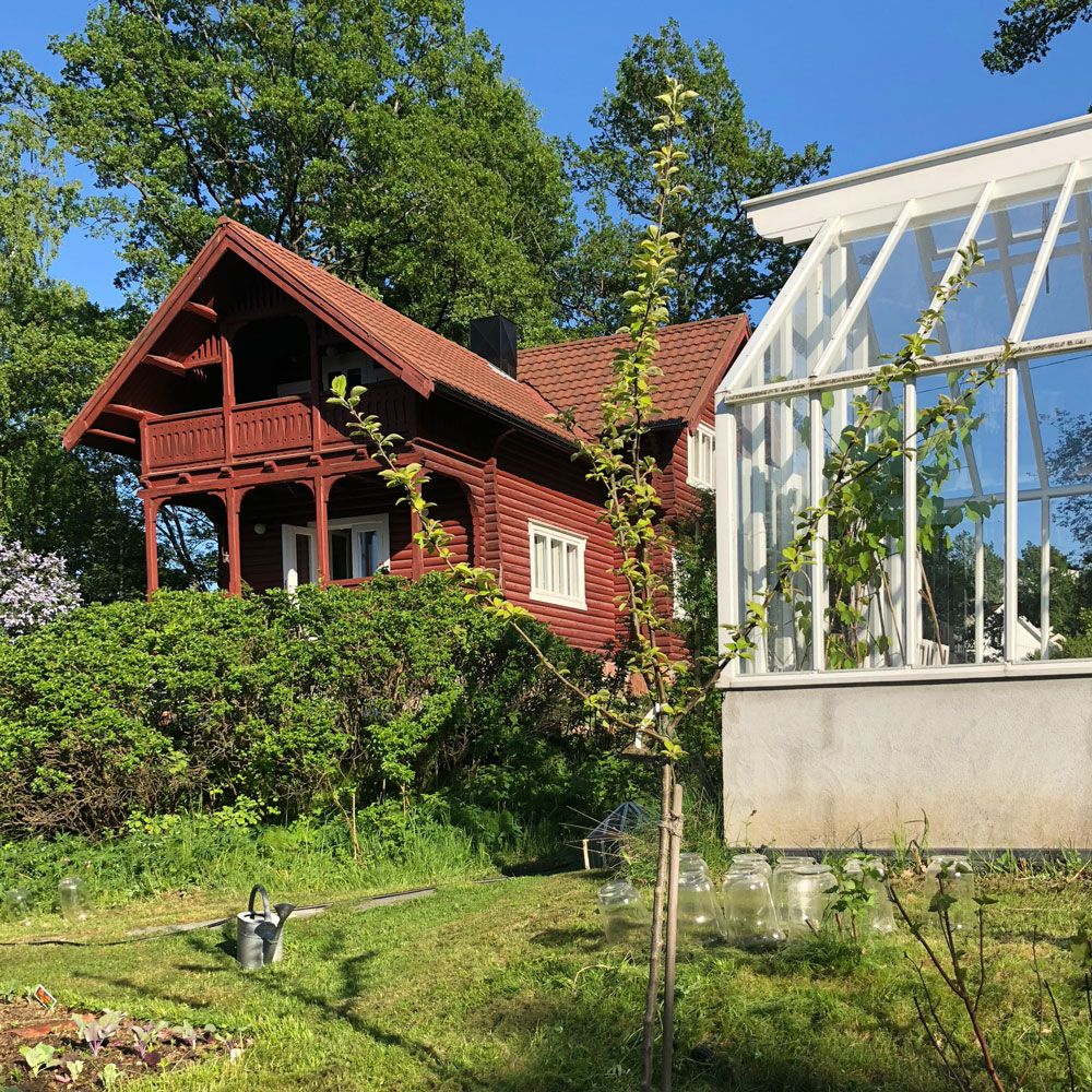Ett växthus i trä och ett rött hus i norsk drakstil.