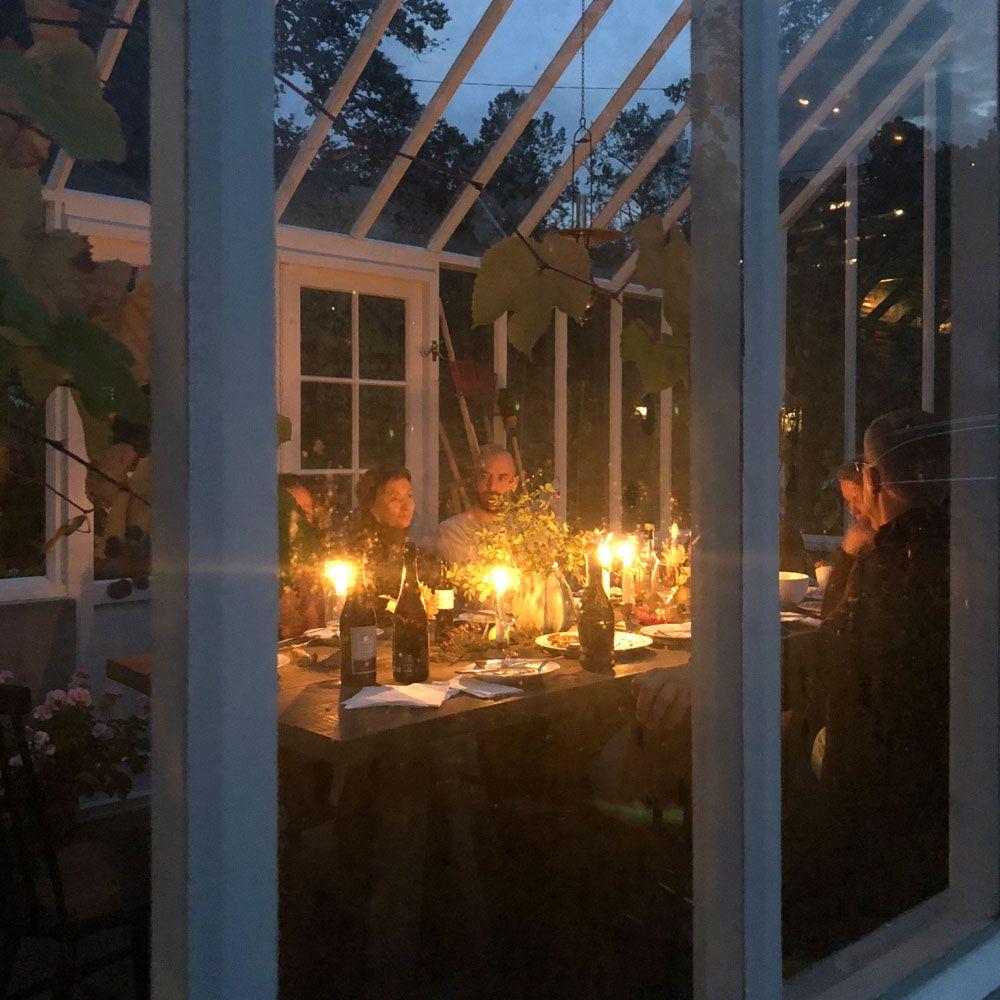 Middagsgäster i ett vitt växthus i kvällsljus.