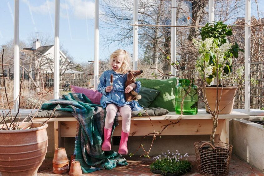 En flicka på en bänk omgiven av växter i växthus.