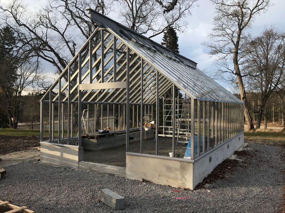 Ett halvklart gråmålat växthus med sadeltak.