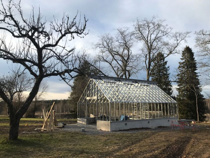 Ett stort gråmplat växthus i trä och glas.