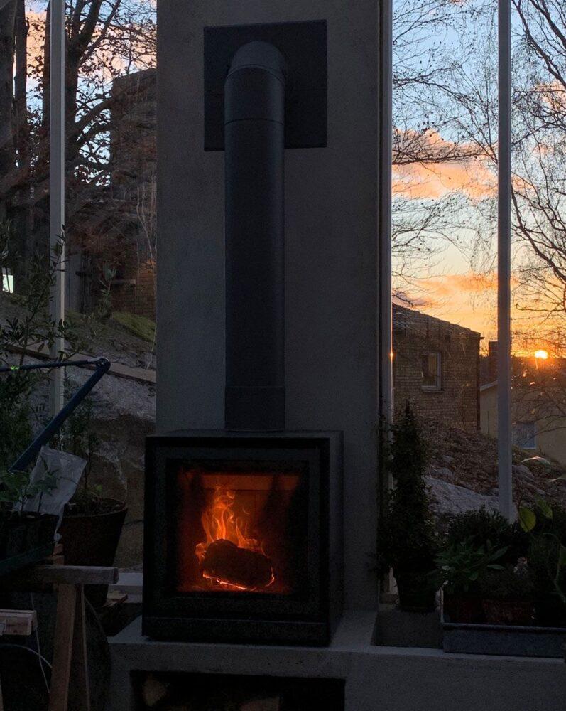 Öppen spis i solnedgång i växthus.