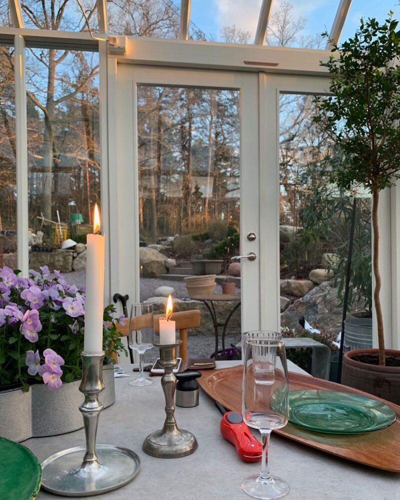 Tända mässingsljusstakar på bord i växthus.