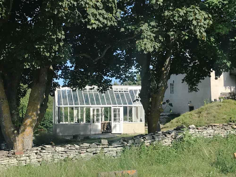 Ett växthus med sadeltak bakom en mur under ett par träd.
