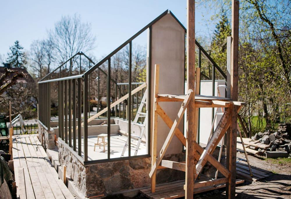 Byggställning i trä framför växthus i trä.