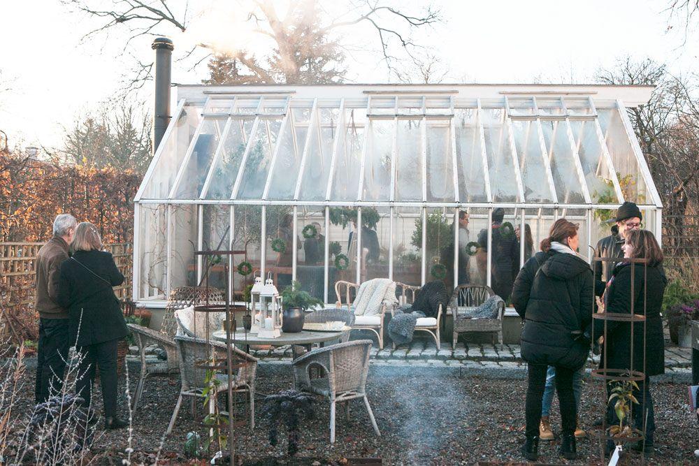 Svartklädda kvinnor och män runt ett växthus.