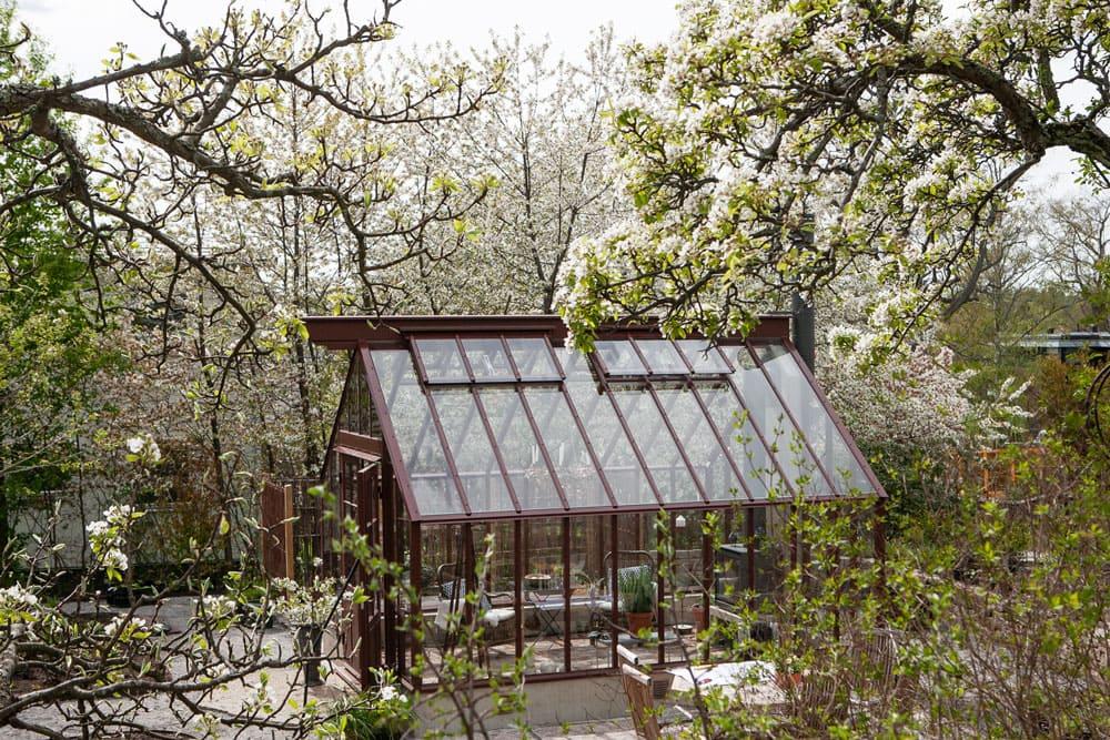 Ett brunt växthus med sadeltak.