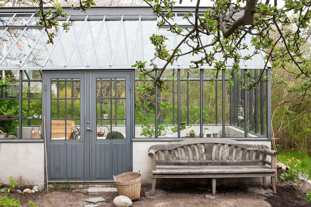 Trädgårdssoffa i teak framför grått växthus.