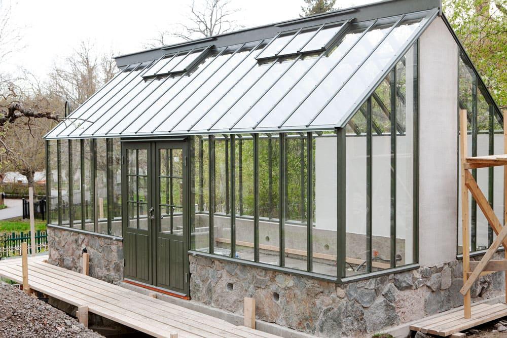 Ett grönt växthus på granitgrund.