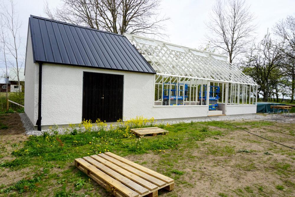Ett vitt stort växthus med förråd