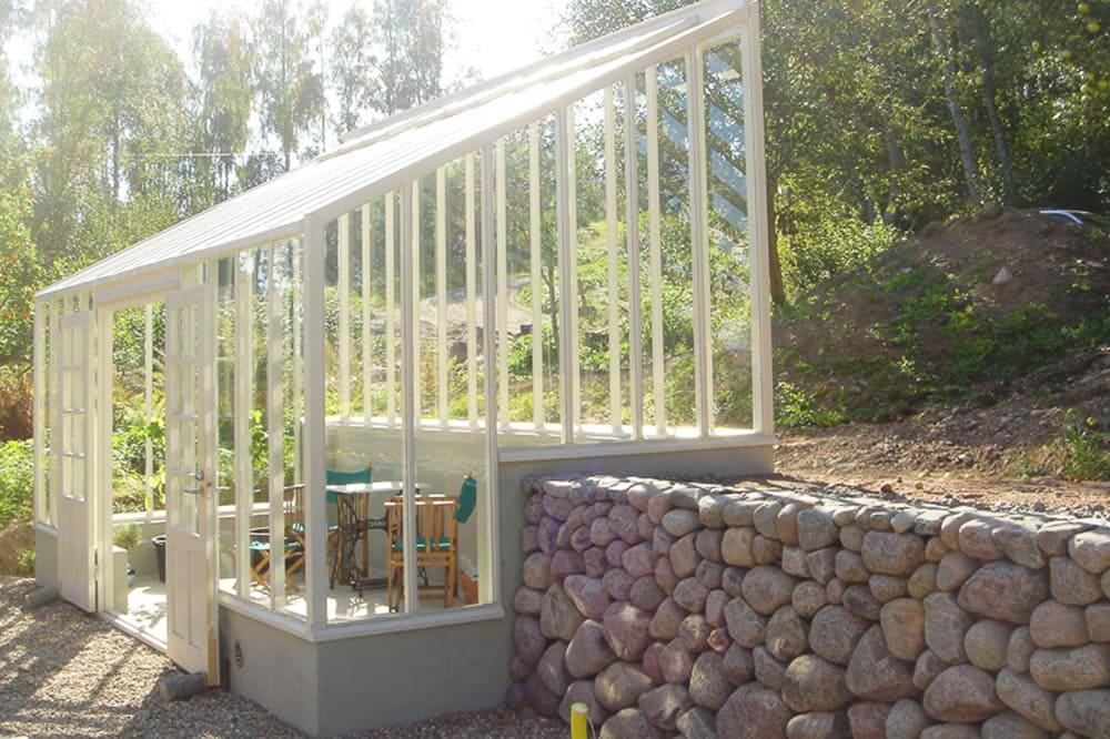 Vitt växthus med pulpettak på kullerstensmur.