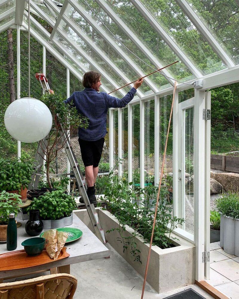 Man monterar kopparrör i taket på ett växthus.