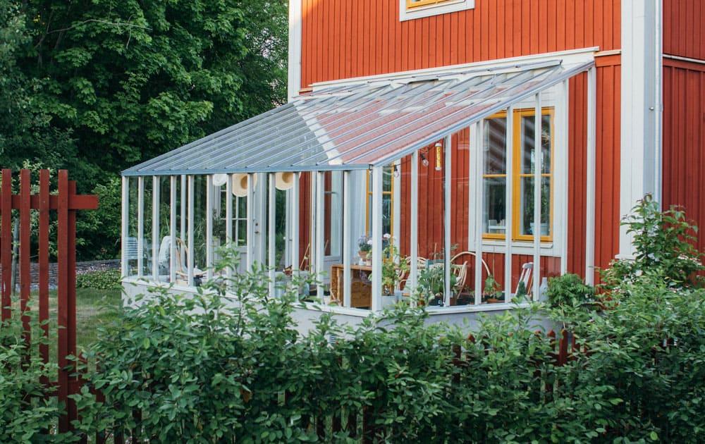 Ett växthus med pulpettak mot rött bostadshus.