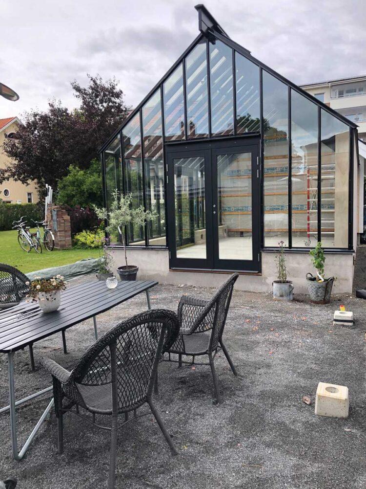Ett bord med stolar framför ett växthus