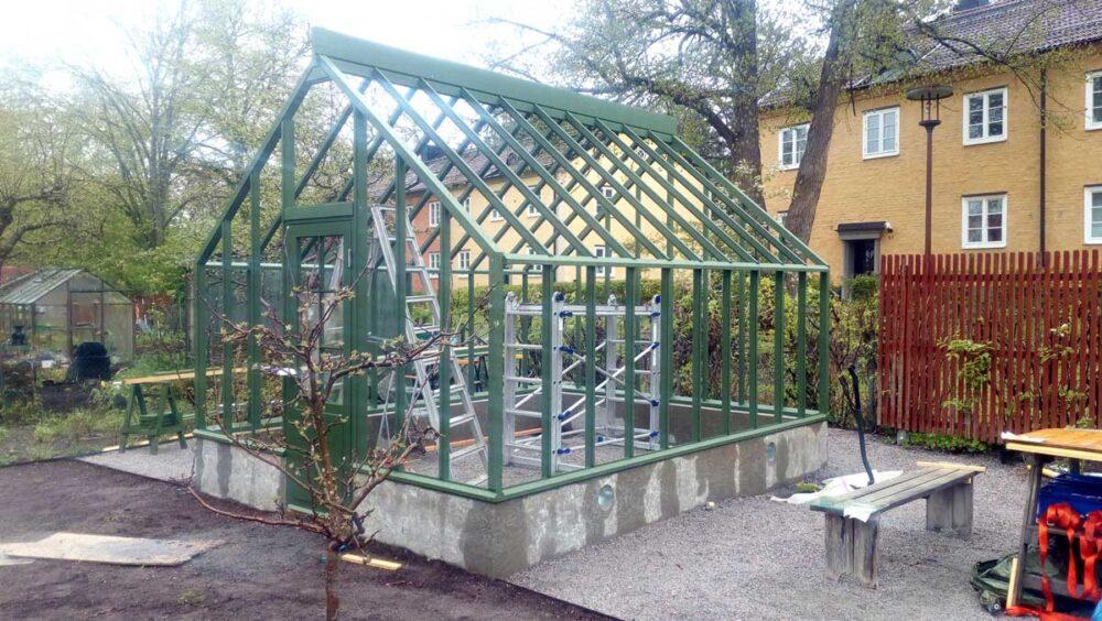 Ett grönt växthus med en bänk bredvid