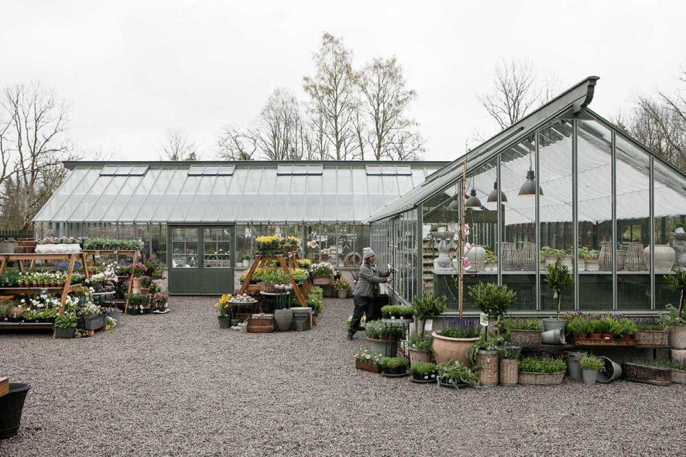 En kvinna stänger växthusdörr
