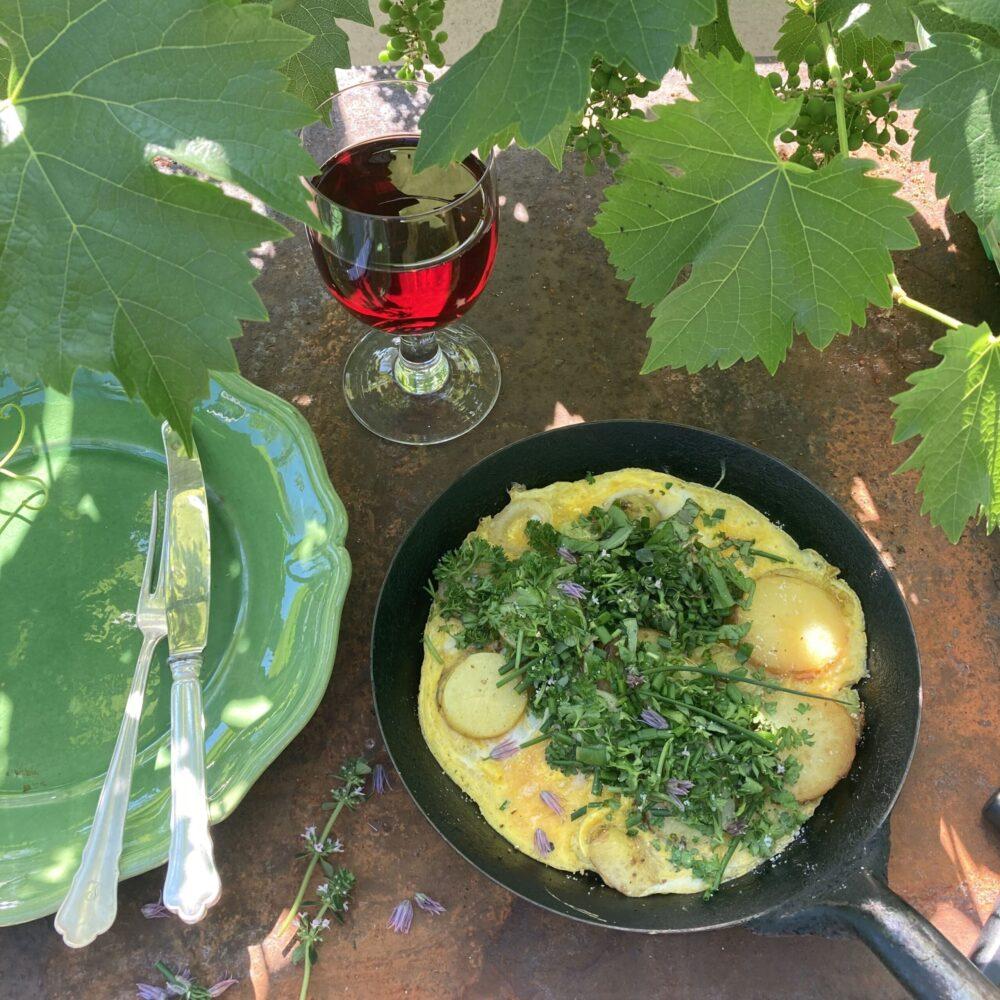 Stekpanna med omelette och grön tallrik med bestick.