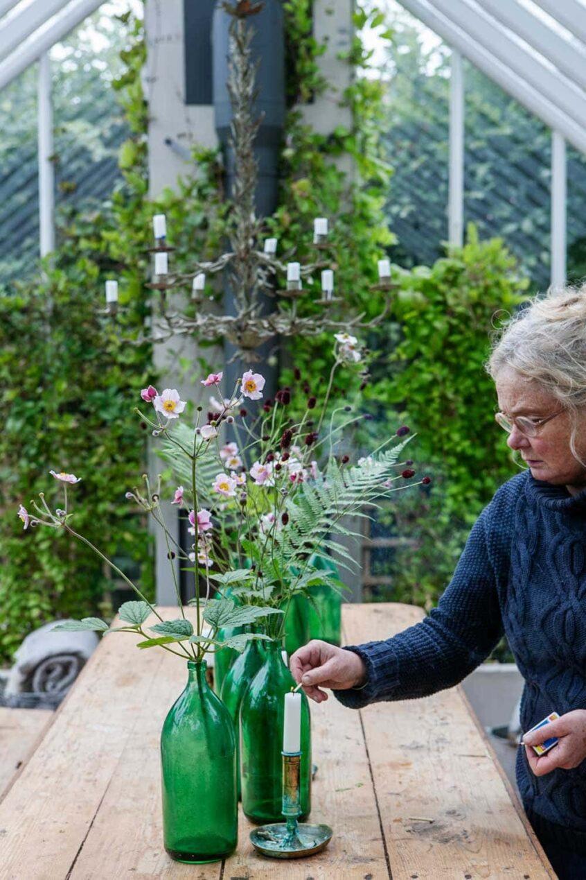 Kvinna framför bord i växthus.