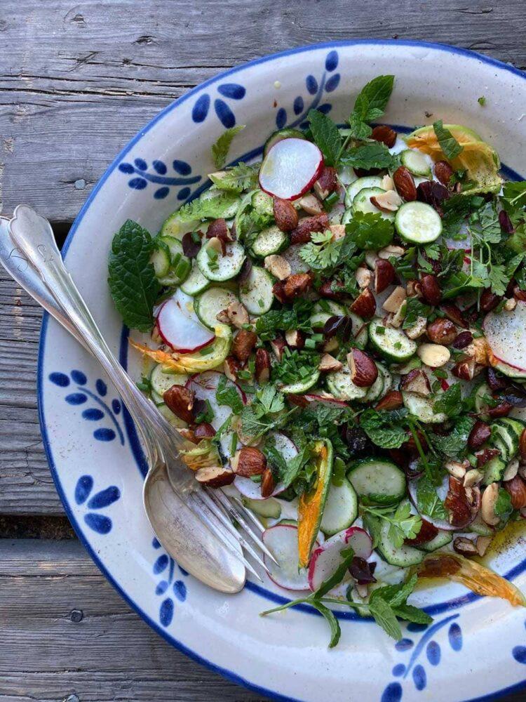 sallad med zucchini och mandlar på blåvitt fat.